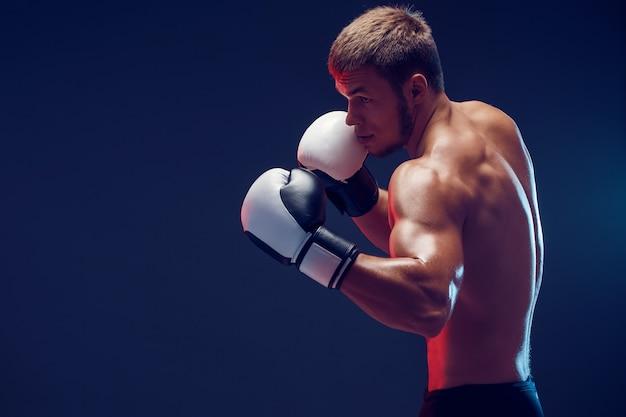 Boxeador sin camisa con guantes sobre fondo oscuro. aislar