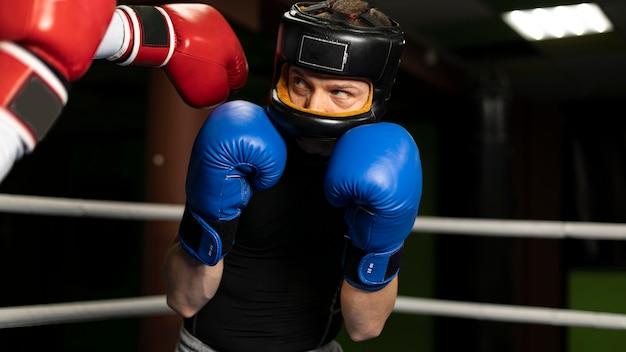 Boxeador con casco y guantes de entrenamiento.