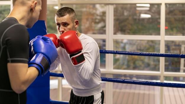 Boxeador con casco y guantes entrenando con hombre