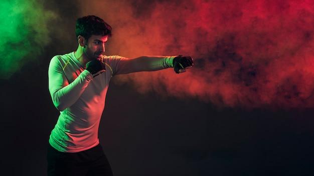 Boxeador concentrado golpeando en la oscuridad
