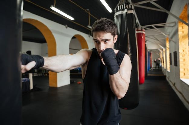 Boxeador concentrado haciendo entrenamiento con saco de boxeo