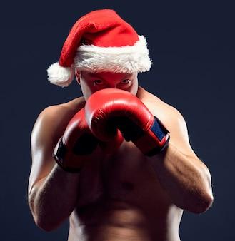 Boxeador de fitness de navidad con gorro de papá noel y guantes rojos de boxeo sobre fondo negro
