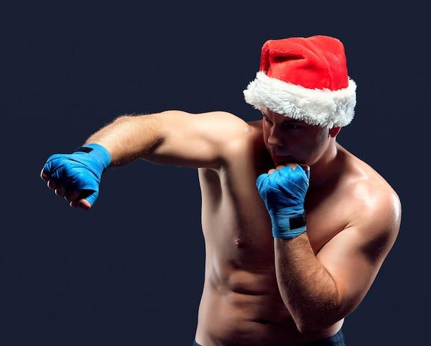 Boxeador de fitness de navidad con sombrero de santa boxeo en negro