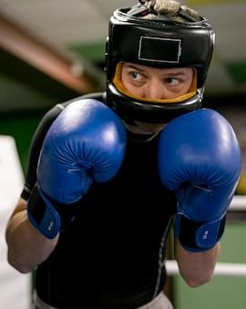 Boxeador con guantes y casco de entrenamiento en el ring.