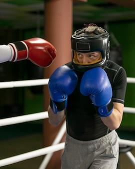 Boxeador con guantes y casco de entrenamiento.