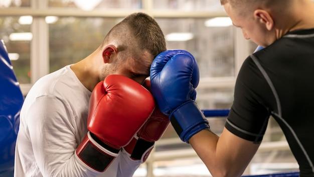 Boxeador con guantes entrenando con hombre en el ring