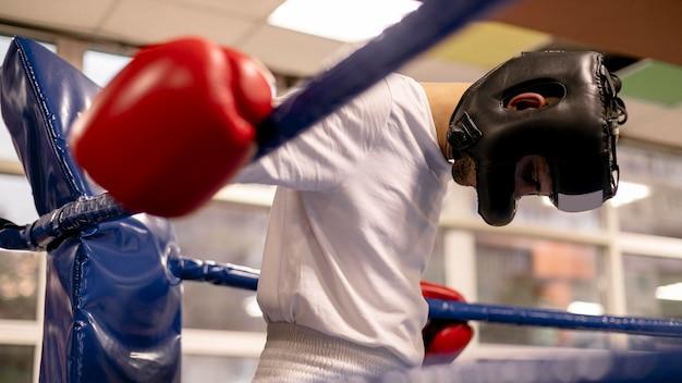 Boxeador masculino con casco y guantes en el ring practicando
