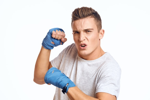 Boxeador masculino deportivo en guantes azules practicando golpes en una pared de luz