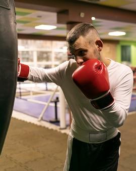 Boxeador masculino practicando con saco de boxeo