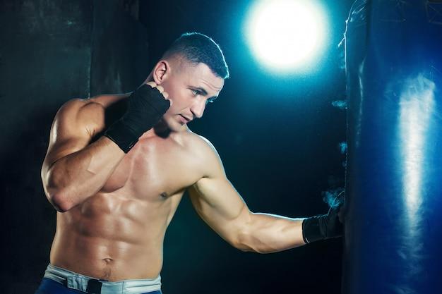 Boxeador masculino en saco de boxeo con espectacular iluminación vanguardista