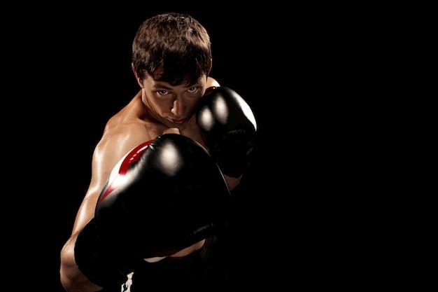 Boxeador masculino en saco de boxeo con iluminación dramática