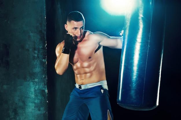 Boxeador masculino en saco de boxeo