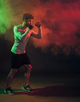 Boxeador serio en guantes de entrenamiento en el humo