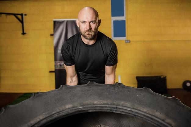 Boxeador tailandés levantando neumáticos pesados