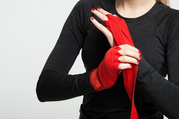 La boxeadora se envuelve las manos con envolturas de boxeo rojas. aislado sobre fondo blanco con espacio para texto
