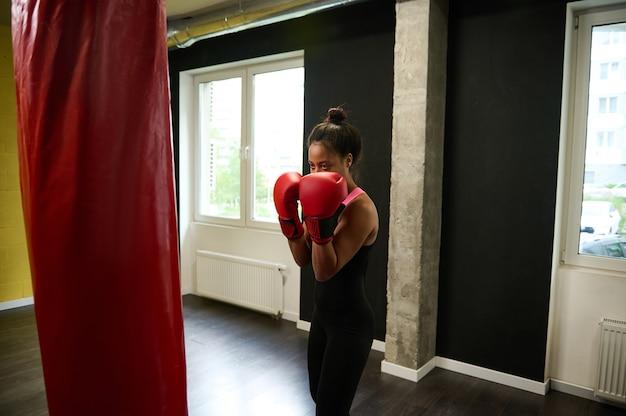 Boxeadora de fitness en ropa deportiva negra ajustada y guantes de boxeo rojos entrenando en un gimnasio de boxeo, haciendo un golpe directo golpeando un saco de boxeo durante un entrenamiento en interiores