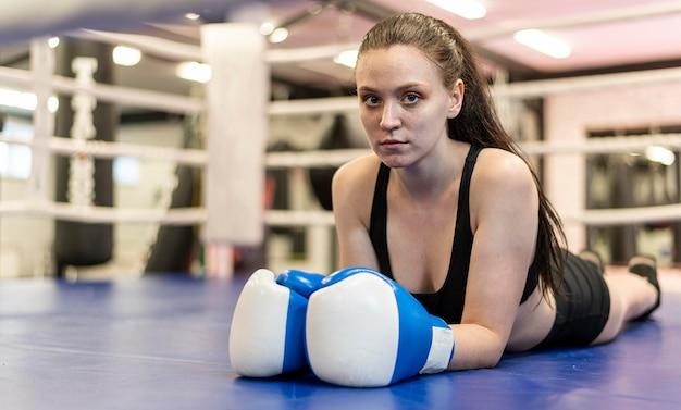 Boxeadora con guantes protectores posando en el suelo
