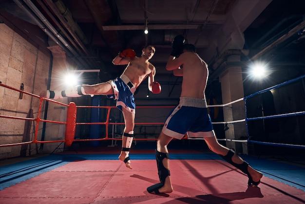 Boxeadores entrenando kickboxing en el ring en el club de salud