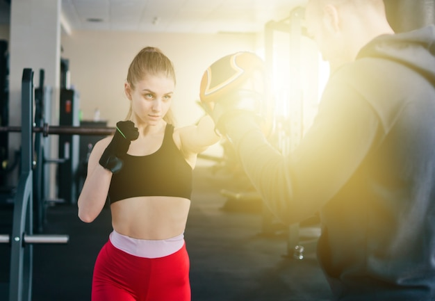 Boxeo femenino joven en el gimnasio con instructor masculino. pareja, ejercitar, puñetazos