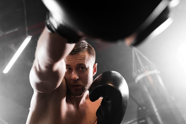 Boxer de ángulo bajo con guantes negros de entrenamiento