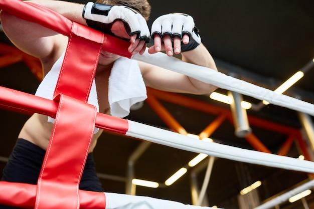 Boxer cansado descansando contra cuerdas de anillo