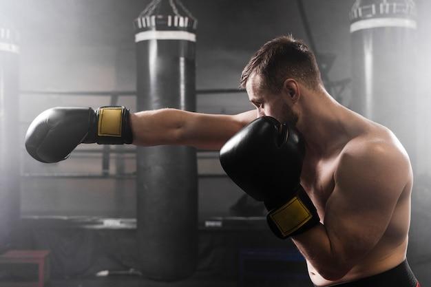 Boxer lateral con guantes negros de entrenamiento