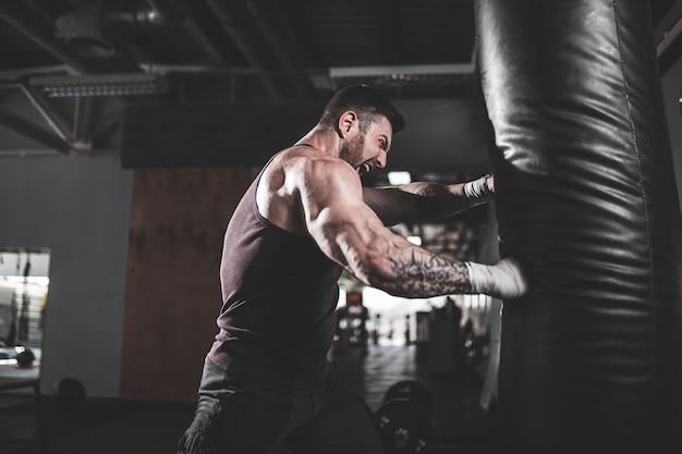 Boxer masculino entrenamiento con saco de boxeo en el pabellón deportivo oscuro.