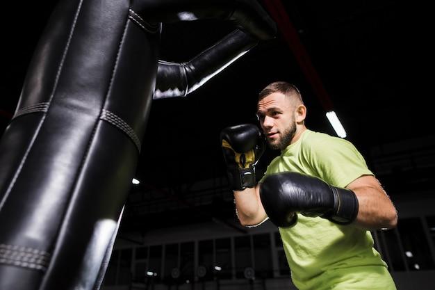 Boxer masculino en guantes de protección con saco de boxeo