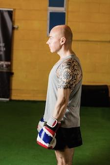 Boxer de pie con guantes de boxeo en el gimnasio