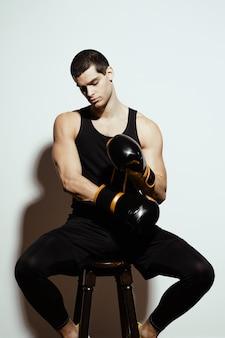 Boxer poniéndose los guantes de boxeo mientras descansa en la silla