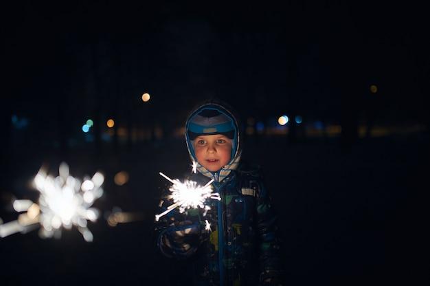 Boy sostiene una bengala en sus manos mientras celebra un año nuevo en la calle por la noche.