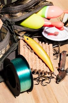 Boya en bolsa; señuelos de pesca y carretes de pesca en el escritorio de madera.