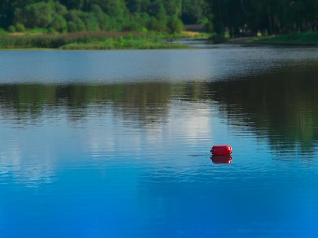 Boya roja sobre fondo de río de verano