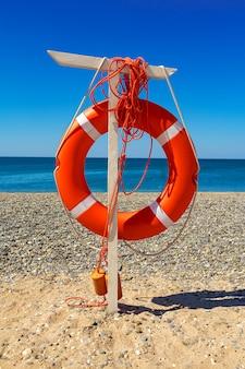 Boya de vida en la playa contra el mar