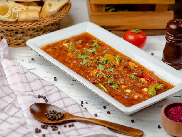 Bozbash tradicional, harina de carne con salsa de tomate y pimiento en plato blanco.