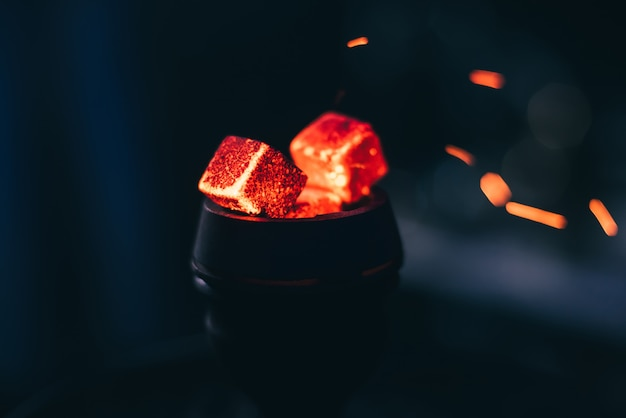 Brasas rojas para la cachimba con chispas sobre fondo oscuro