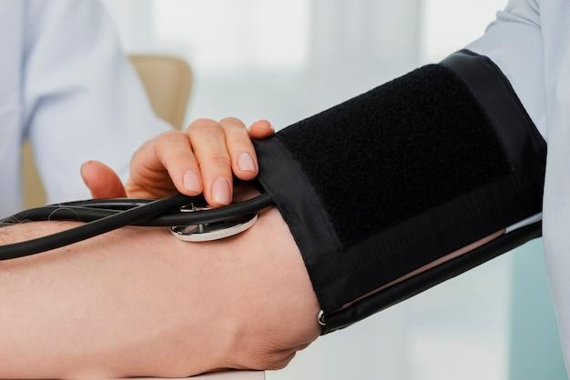 Brazalete de presión arterial en el brazo del paciente