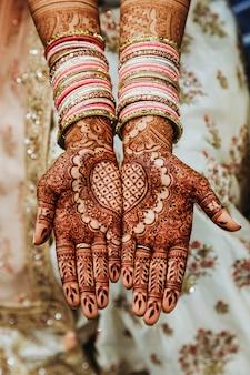 Brazaletes de boda indios y manos de color mehandi henna con adornos reflectantes