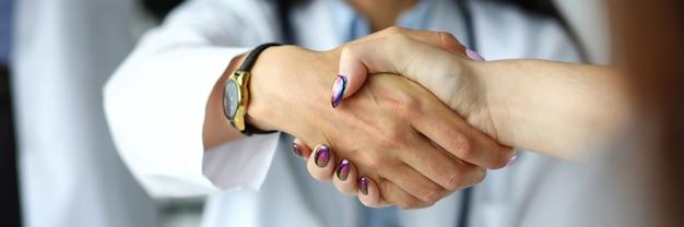 Brazo de doctora estrechándole la mano con visitante