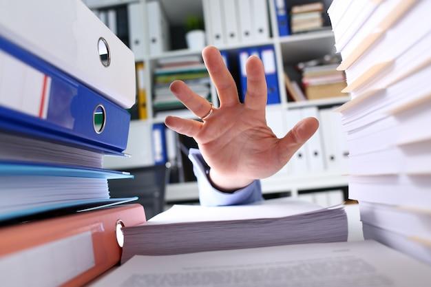 Brazo de empleado masculino tratando de alcanzar la parte superior de la pila de papel desde abajo