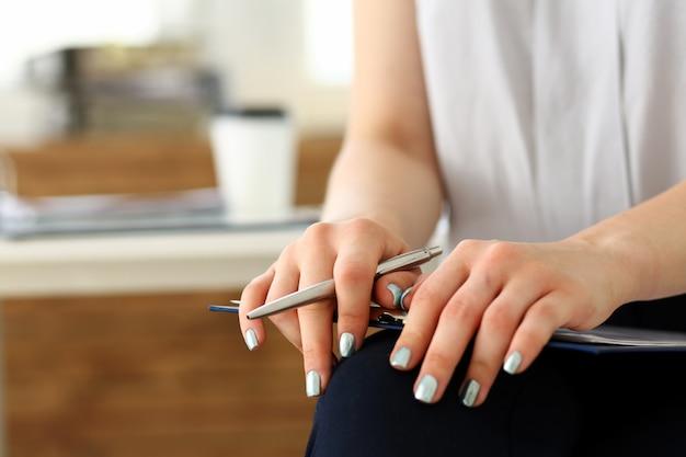 Brazo femenino en traje sujeta bolígrafo plateado