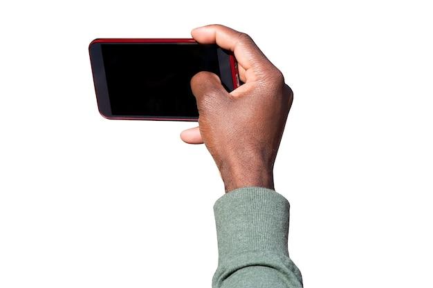 Brazo de un hombre afroamericano tomando fotos por dispositivo móvil y tocando la pantalla del teléfono móvil aislado sobre fondo blanco.