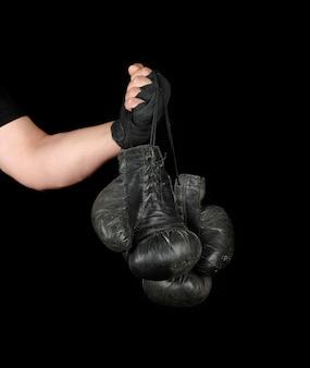 El brazo de los hombres envuelto en un vendaje deportivo elástico negro contiene un par de guantes de boxeo de cuero antiguos.