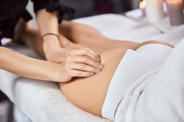 Brazo masajista masajeando el culo de la mujer en bragas blancas en el salón de belleza