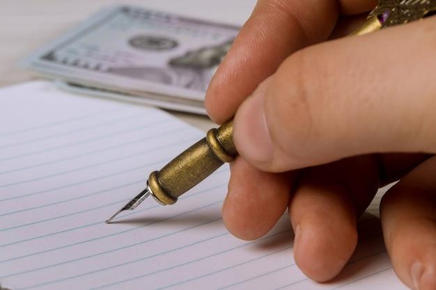 Brazo masculino que hace notas de la libreta con una pluma y dólares de ee. uu.