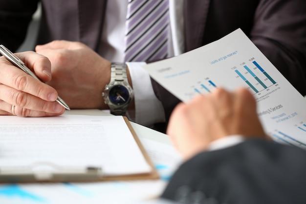 El brazo masculino en traje y corbata rellena la almohadilla recortada con un primer plano de plata.
