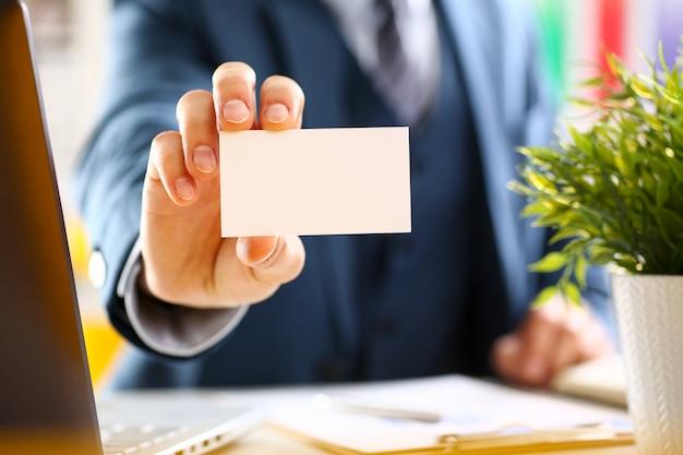 El brazo masculino en traje da la tarjeta de visita en blanco al primer del visitante.