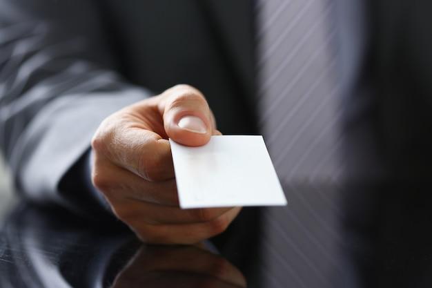 Brazo masculino en traje dar tarjeta de visita en blanco