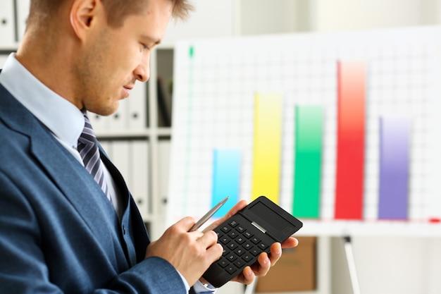 Brazo masculino en traje mantenga calculadora presionando botones