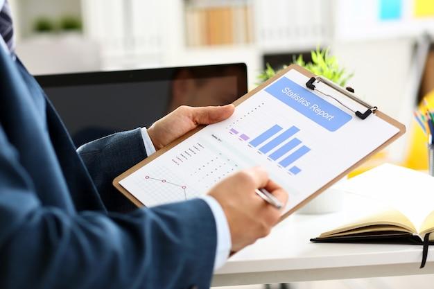 Brazo masculino en traje muestra el gráfico de estadísticas recortado en la almohadilla